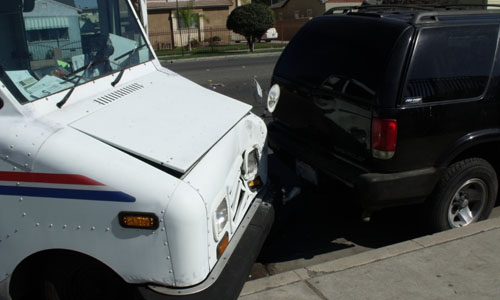 US Postal Truck strikes Parked Vehicle